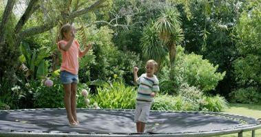 Bruder und Schwester springen in Zeitlupe auf Trampolin
