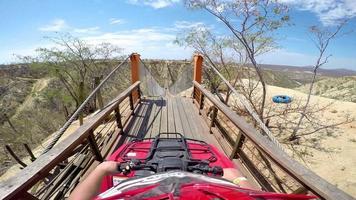 first person pov van een vierwieler die op het punt staat over een hangende brug te rijden video