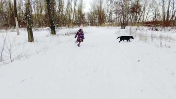 petite fille jouant avec son labrador noir sur la neige