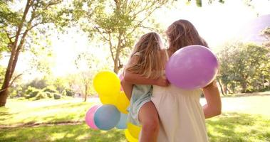 Happy mother and daughter in park with colorful balloons