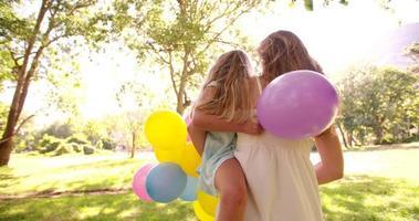feliz madre e hija en el parque con globos de colores