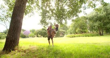 padre moderno che gioca con i figli sull'altalena nel parco video