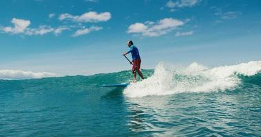 surfista sull'onda blu dell'oceano cavalca lungo la linea
