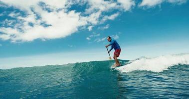 surfista sull'onda blu dell'oceano che appende dieci sul longboard