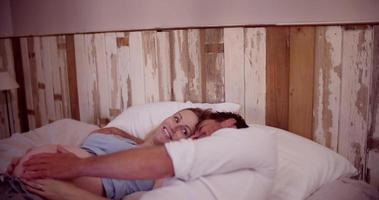 Paar, das im Bett liegt und den schwangeren Bauch der Frau berührt