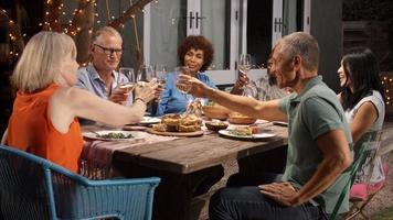Gruppe reifer Freunde, die Mahlzeit im Freien im Hinterhof genießen