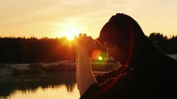 o jovem sonha ao pôr do sol. ele está no capô: sentado de perfil para a câmera video