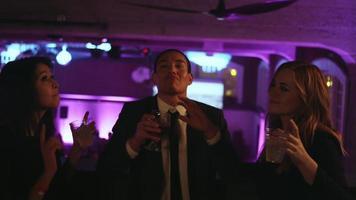 un grupo de amigos en el balcón de una discoteca sosteniendo bebidas y bailando, cámara lenta video