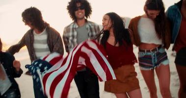 Hipster friends walking on the beach holding an American flag