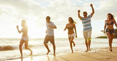 amigos na praia ao pôr do sol