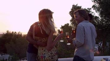 due coppie su un tetto che fanno un brindisi al tramonto, scatto r3d