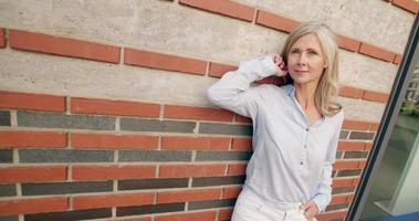 donna matura dai capelli grigi sorridente contro un muro strutturato