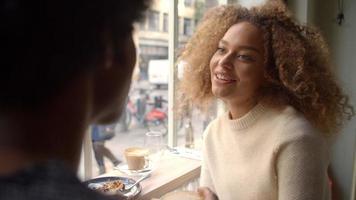 Elegante pareja joven disfrutando de una bebida en la cafetería. video