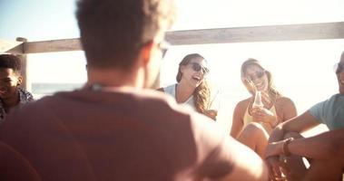 gruppo di amici rilassarsi e bere birra in spiaggia video