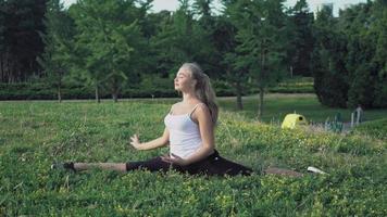 menina loira sentada em uma colina e fazendo os exercícios vira à direita e à esquerda video