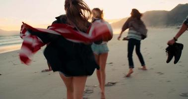 Hipster friends run at the beach and holding an American flag