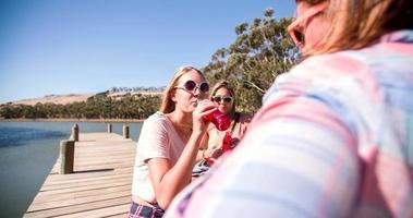 ragazze adolescenti che ridono su un molo durante una pausa estiva