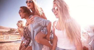 ragazzo adolescente che trasporta sulle spalle la sua ragazza all'aperto con gli amici