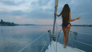 ragazza con i capelli lunghi che gode di una crociera su uno yacht a vela. video