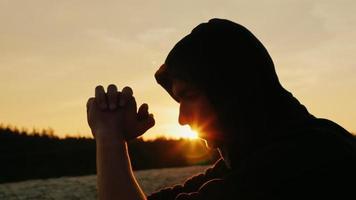 sognatore al tramonto. un giovane si siede nel profilo del cofano alla telecamera. è pensieroso, i raggi del sole si fanno strada dal suo viso