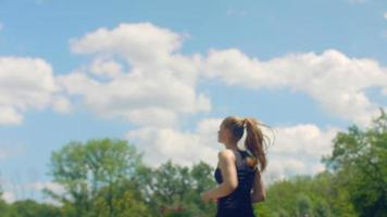 femme de remise en forme en cours d'exécution au ralenti au fond de ciel bleu avec des nuages
