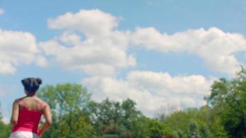 fille jogging au ralenti au fond de ciel bleu avec des nuages