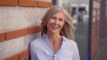 donna matura con i capelli grigi su una strada cittadina sorridente