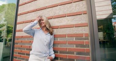 reife Frau mit grauem Haar auf einer Stadtstraße lächelnd