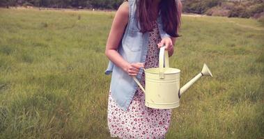 donna felice versando acqua sui fiori