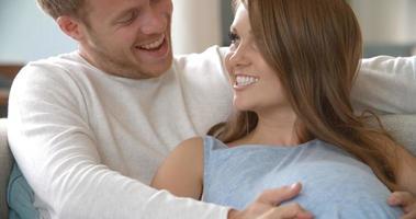 coppia con donna incinta rilassante sul divano girato su r3d