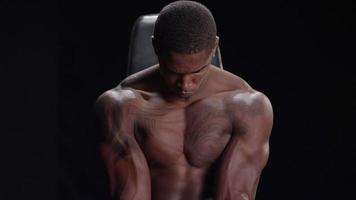 muskulöser schwarzer Mann, der zwischen Trainingseinheiten ruht
