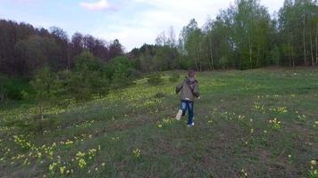 muchacho adolescente corriendo por el césped en el bosque. el chico tiene buen humor.