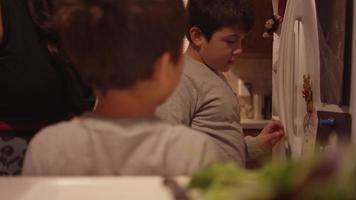 um garotinho colocando sua arte na geladeira