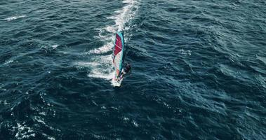 Aerial view of windsurfer gliding across blue ocean