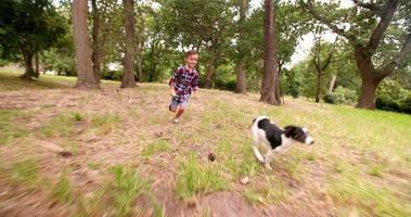 Niño persiguiendo a su perrito corriendo en el parque con pelota