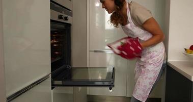 Frau, die heiße Kekse aus dem Ofen nimmt