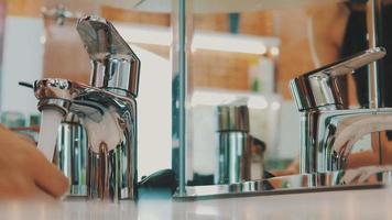 offenes Wasserhahn des Waschbeckens des jungen Mädchens im vorderen Spiegel im Badezimmer. Wasser. Morgen