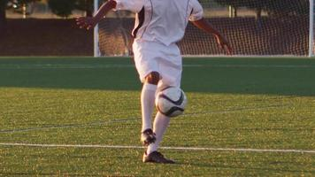 A soccer player juggles a ball at sunset