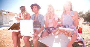 amici che ridono e si godono la pizza in una giornata estiva