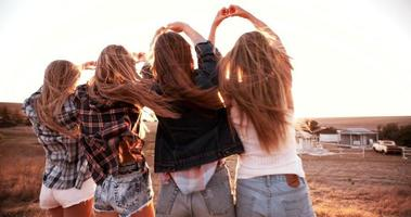 ragazze adolescenti che fanno forme di cuore con le mani al tramonto