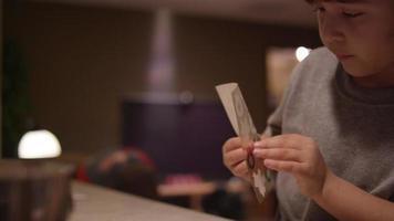 Un garçon assis au comptoir de la cuisine, mettant un autocollant de Noël sur un morceau de papier