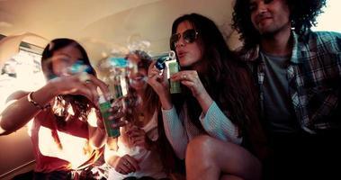amici hipster che fanno festa con le bolle all'interno di un furgone vintage