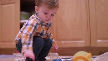 kleine jongen speelt met plasticware in de keuken en wrijft in zijn ogen en ziet er moe uit