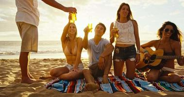 amis se détendre sur la plage au coucher du soleil