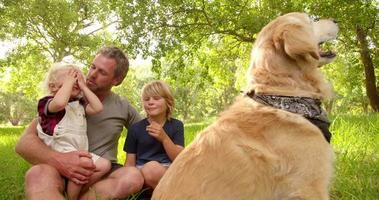 Dad plays with his cute sons and their dog outside video