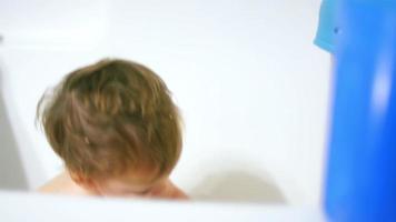 adorável garotinho espirrando água e enchendo um copo na banheira