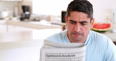 Mann liest Zeitung und trinkt morgens Kaffee