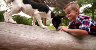 lachende jongen liggend op log in natuur geconfronteerd met puppy hondje