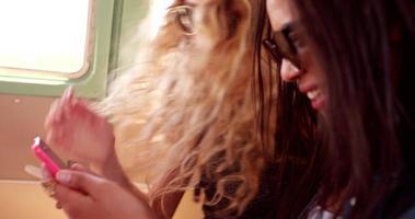 due ragazze hipster seduti insieme in furgone guardando il telefono