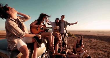 niña adulta joven tocando la guitarra al aire libre con amigos